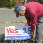 Man setting up 'Yes on 15' sign.